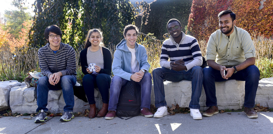 Five students chatting outdoors