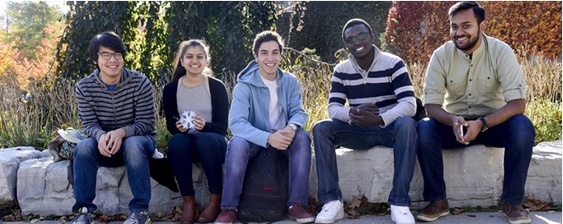 Five smiling students sitting on bench rocks outdoors