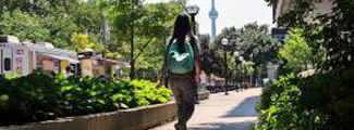 Student with long black hair walking away with CN Tower in distance