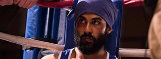 Sikh boxer sitting in corner of boxing ring