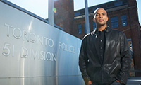 Photo of Professor Owusu-Bempah standing beside the Toronto Police sign