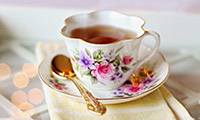 Tea cup with floral pattern on saucer with spoon