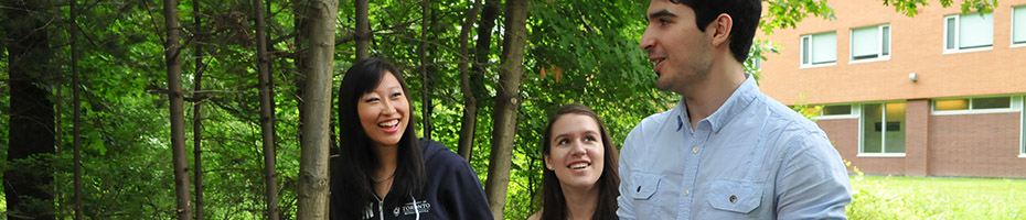 Three students walking through a wooded area