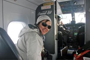 Tracey Galloway inside small aircraft near pilot, turning around to look at camera