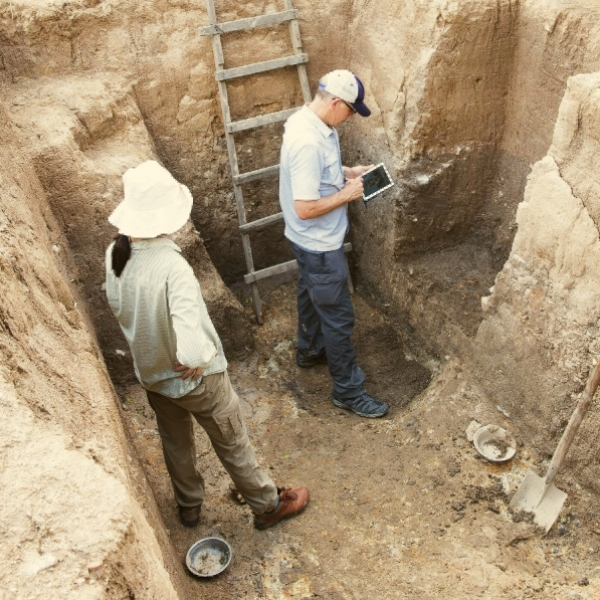 Two archaeologists standing in an excavated archaeological site. Photo © G. Crawford.