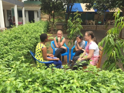 Students in conversation in a garden in Moshi.