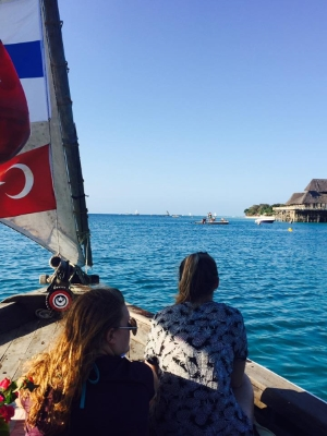 Two students sitting in a sailboat in waters off Zanzibar.