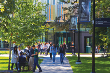 students on campus with trees, grass and buildings