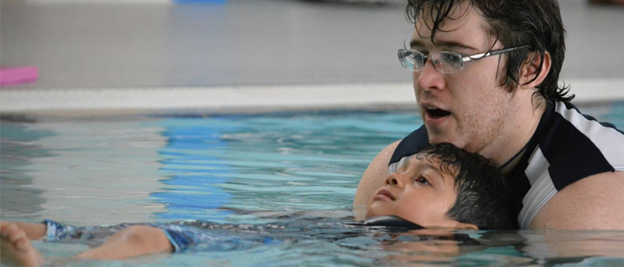 Pre-School Swim Instructor helping a child float