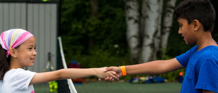 Two Racquet campers shaking hands after a match