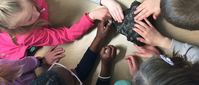 Children exploring a unique rock at Sci-Biz Camp