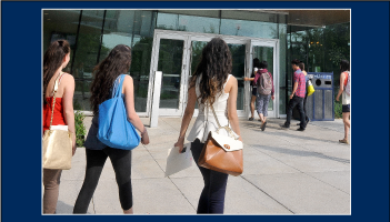 three female students walking to building entrance