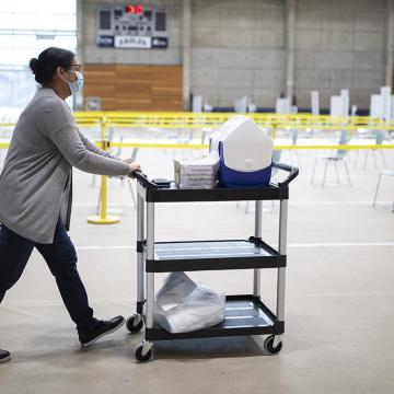 A masked health care worker pushes a trolley of supplies through a vaccination clinic.