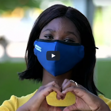 A young Black woman wearing a blue U of T branded face mask makes the a heart symbol with her hands.