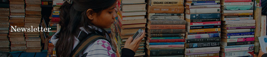 Image of a woman on her cellphone in front of books.