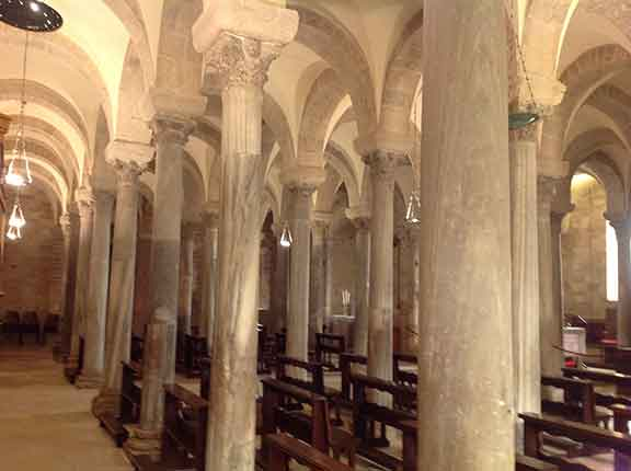 Image description. Crypt of the Cathedral of Trani, est end, showing array of columns reused from earlier sites (spolia) and bright light.
