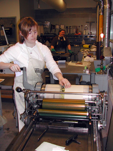 female student working at a printing press