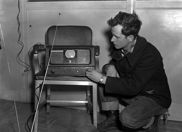 young man inspecting a primitive television
