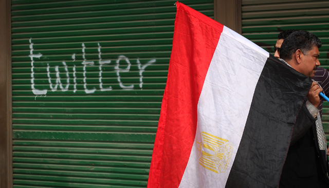 Photograph of middle-aged man carrying Egyptian flag past a garage on with the word twitter has been spraypainted