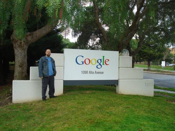 Photo of Anthony standing beside a large Google sign