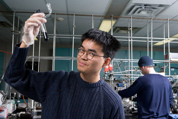 Photo of of Neilson in the lab holding up a test tube