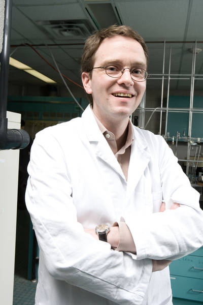 Photo of Ulrich Fekl standing, arms crossed, dressed in lab coat