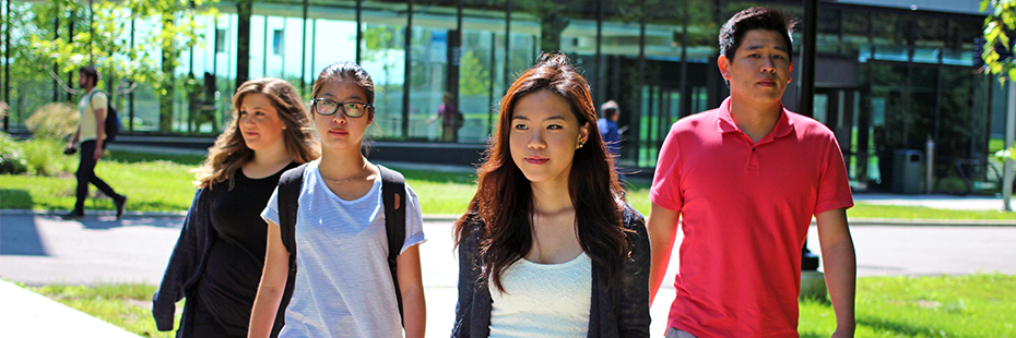 Four students walking the paths around campus