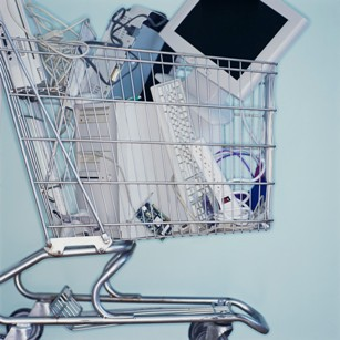 Photo of shopping cart filled with a computer tower, monitor, keyboard and other electronics.