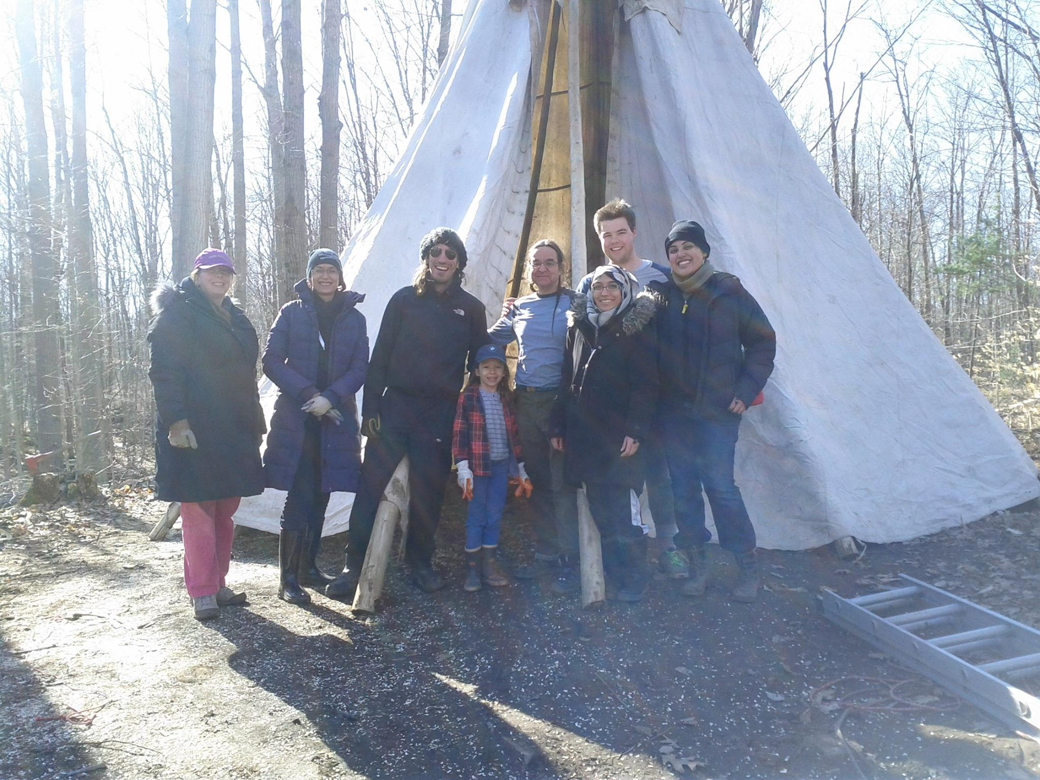 A group of students standing next to a teepee