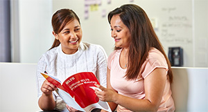 Two students reviewing IELTS materials