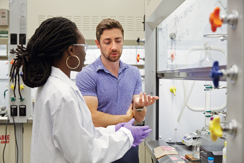 Professor Patrick Gunning and doctoral student Eugenia Duodu talking by chemistry fume hood