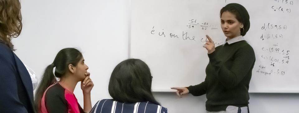 A workshop leader stands in front of a whiteboard facilitating an educational workshop.