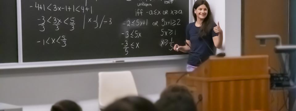 A teacher is in front of a whiteboard with math problems teaching a class.
