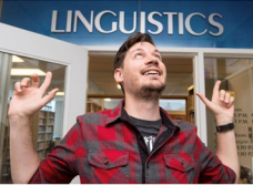 Toronto slang on the rise. Photo of Derek Denis pointing to the Linguistics sign.