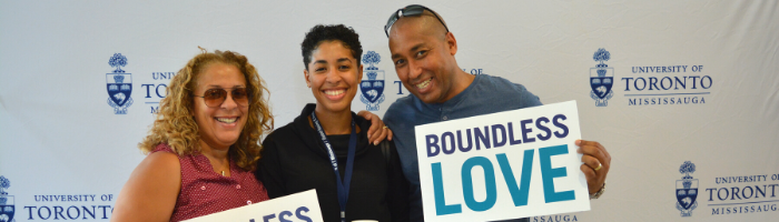 "2 parents and their UTM student smile, with one of the parents holding up a sign that says ""Boundless Love""."