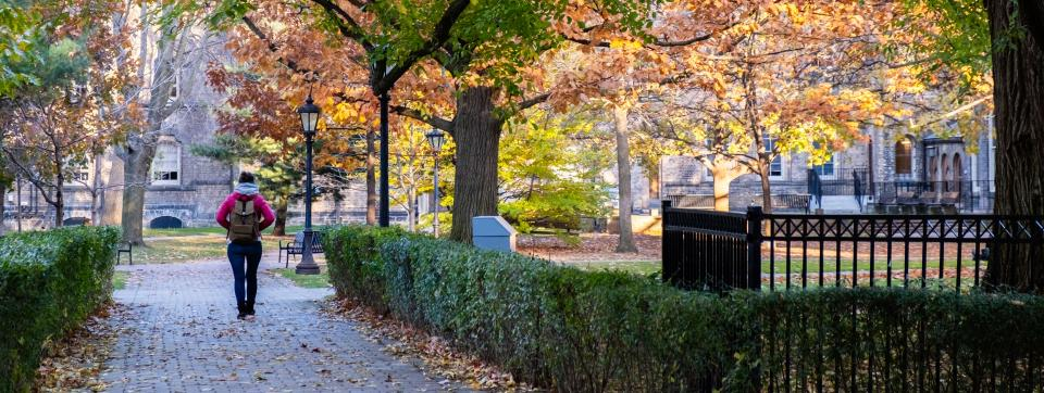 Female student walking on campus path with fall trees and foliage surrounding her