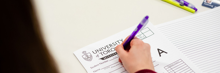 Photo of a student writing filling out their exam booklet