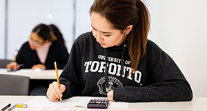 Student wearing a U of T sweater writing an exam