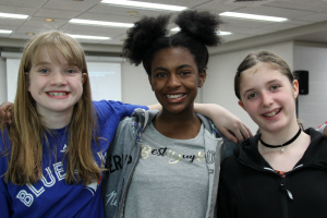 Three teen girls standing together and smiling at the camera