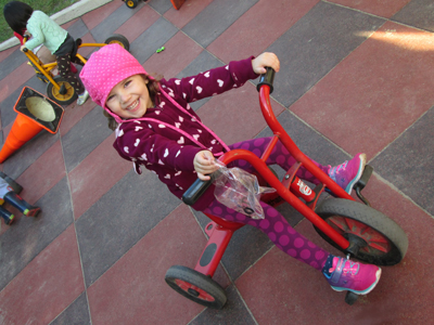 young girl on red tricycle