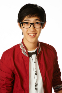 Andre Dae Kim wears glasses and a red cardigan as his Degrassi character Winston Chu.