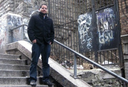 man wearing black standing on steps with graffiti wall