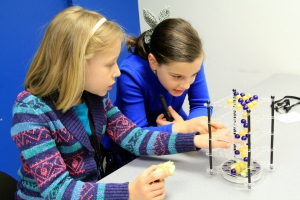 two girls play a game with yellow and blue marbles