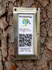 metal tag with black and white QR code nailed to tree bark