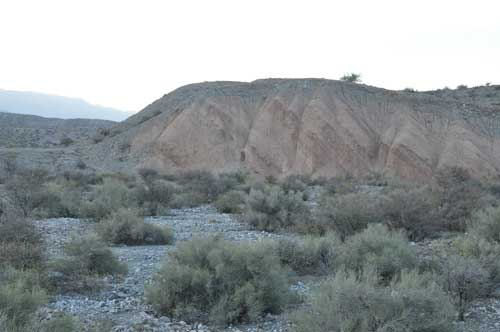 Photo of rocky, hilly terrain and scrub brush.