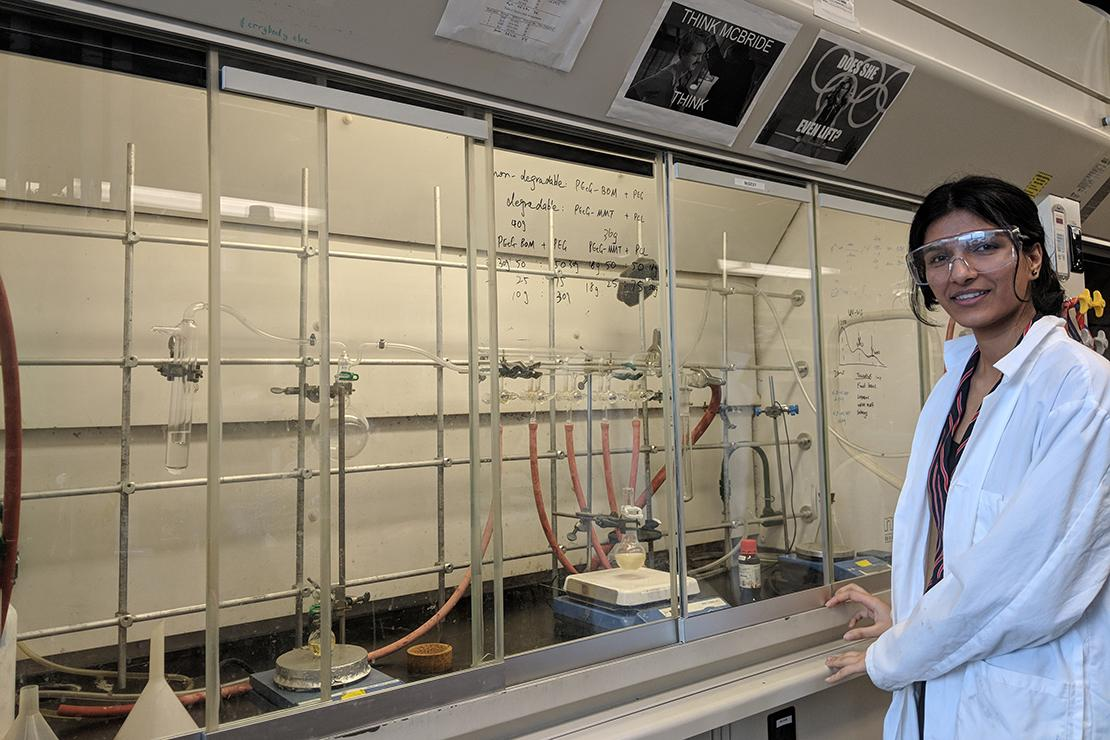 Avneet in lab coat standing next to shelves of beakers