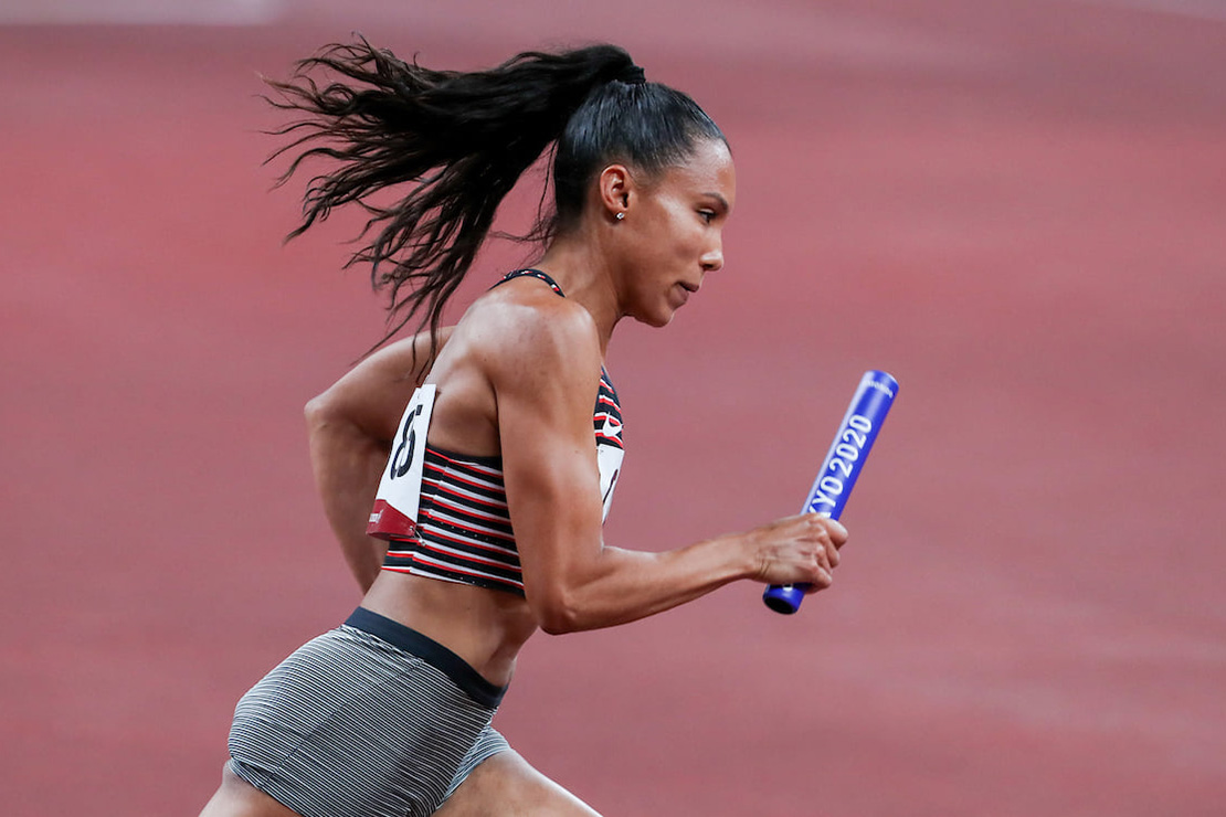 Alicia Brown running, with a paper number on her back and chest, holding a blue baton that reads Tokyo 2020