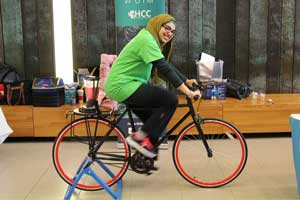 A woman wearing a tan hijab and a green shirt pedals a bike. The bike has a blender mounted over the back wheel blends a pink smoothie drink.