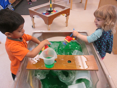 boy and girl playing at water table