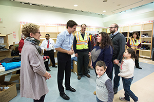 Prime Minister Justin Trudeau welcomes Syrian refugees to Canada at the Toronto Pearson International Airport